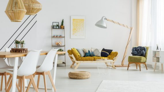 Modern poster hanging on the white wall above mustard sofa
