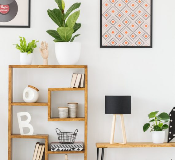 Real photo of a wooden shelf with ornaments in a living room with posters on a wall